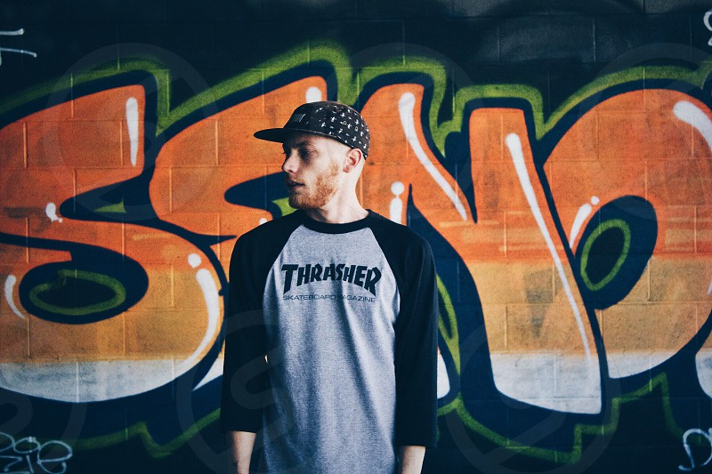 man in thrasher printed baseball long sleeves shirt with a black fitted cap standing at the back of a orange and black wall painting photo