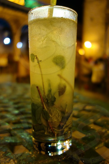 Traditional Cuban Mojito served ice cold at an outdoors terrace in the old town of Havana Cuba. photo