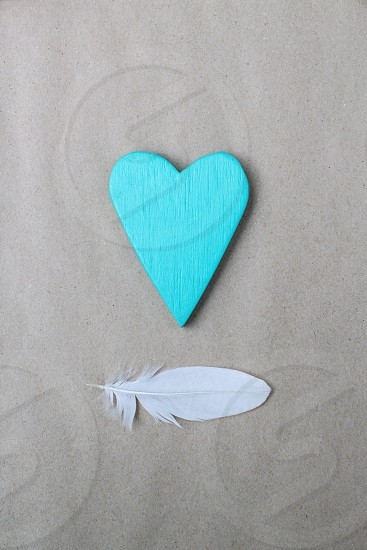 turquoise painted wooden heart and white plumelet on paper background photo