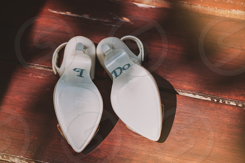 """Women's ivory pump shoes flipped on the wooden floor show the back side with text """"I DO"""" The sun light shading with light and shadow on the floor photo"""
