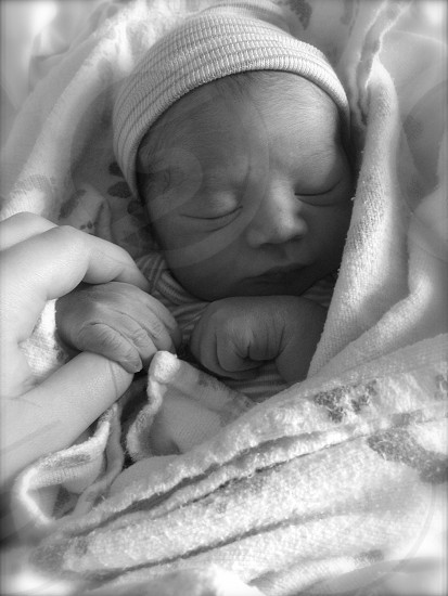 baby sleeping wearing knit cap in black and white photograph photo