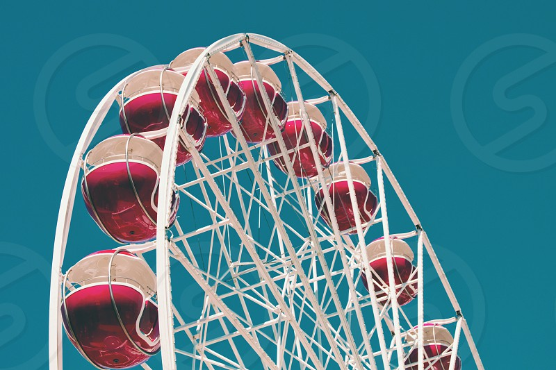White ferris wheel with red carts during daytime. photo