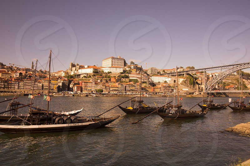 the port wine Boats at the waterfront with the Ponte de Dom Luis 1 and the old town on the Douro River in Ribeira in the city centre of Porto in Porugal in Europe. photo