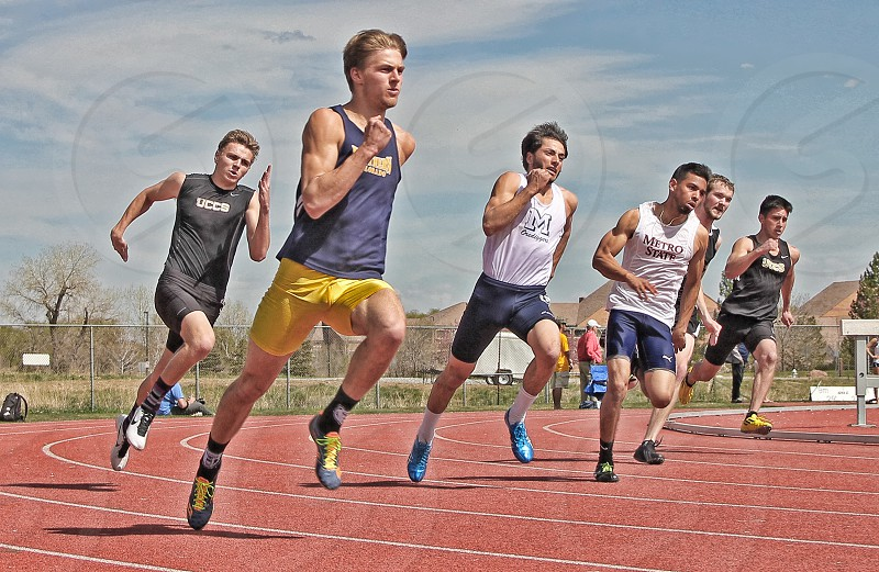 athletes running on track field during daytime photo