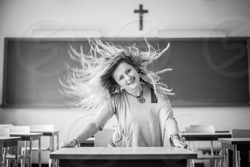 Beautiful alternative girl flipping her hair in class in school with a blackboard in the background in black and white photo