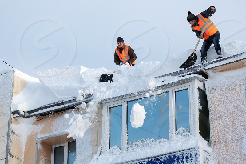 PETROPAVLOVSK CITY KAMCHATKA PENINSULA RUSSIA - DEC 27 2017: Workers with snow shovels carry out winter cleaning of roof of building from snow and ice after heavy snow cyclone (snowstorm blizzard) photo