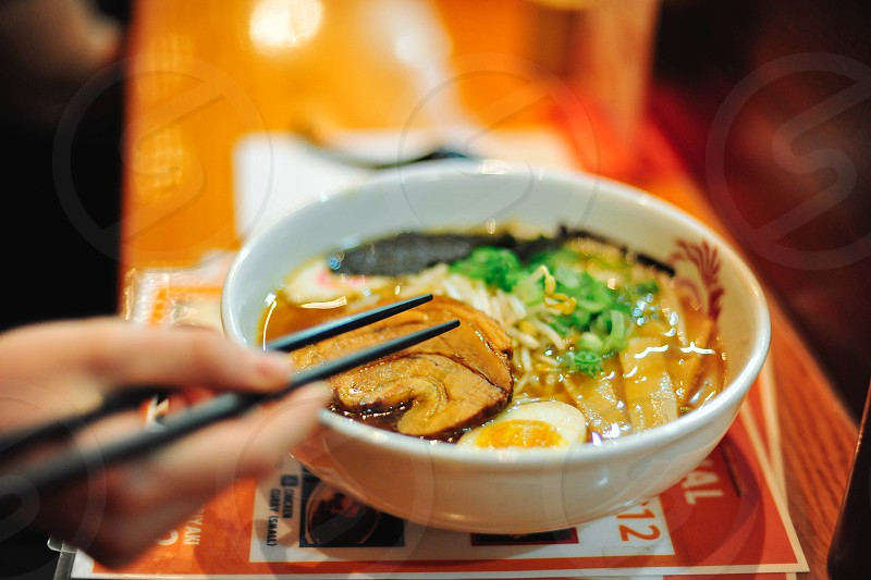 person holding chopsticks over pho noodle soup in a white bowl photo