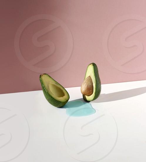 green avocado sliced into halves exposing seed photo