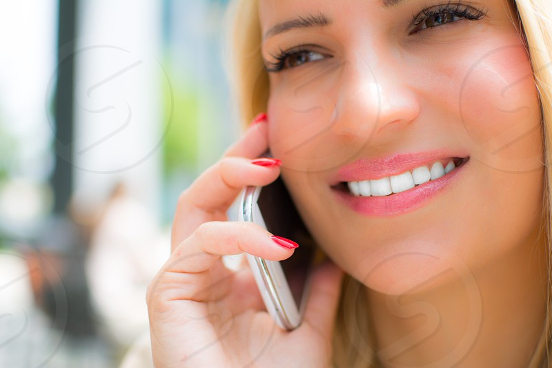 Pretty woman with blonde hairgentle face and blond hair talking on the mobile phone photo