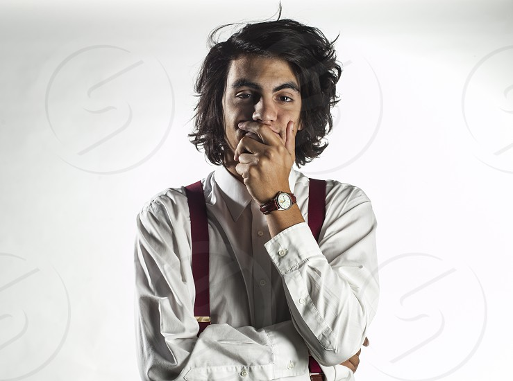 man wearing a white oxford shirt and red suspenders hand over his mouth photo