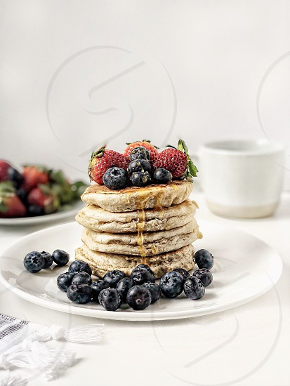 Pancake stack with fresh blueberries strawberries and manuka honey drizzle photo