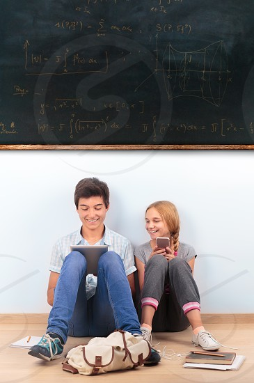Teenagers learning by a blackboard at school photo