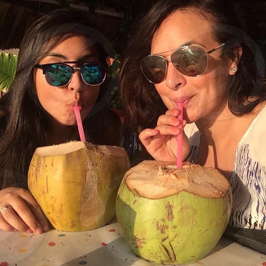 two women drinking buko fruit photo