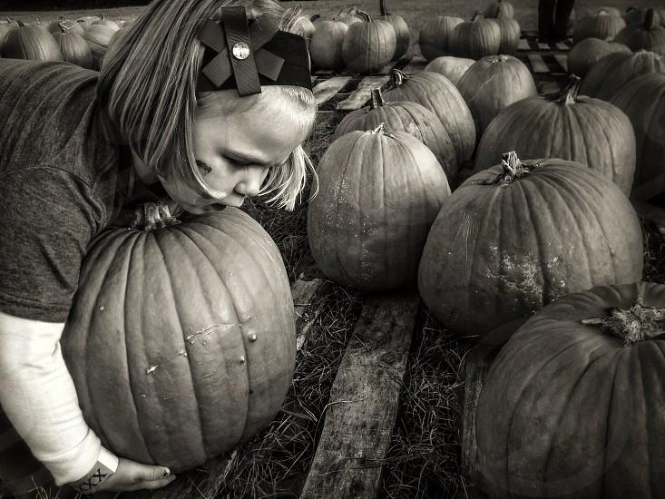 girl with short hair picking pumpkins photo