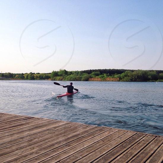 person in red kayak paddling at the lake photo