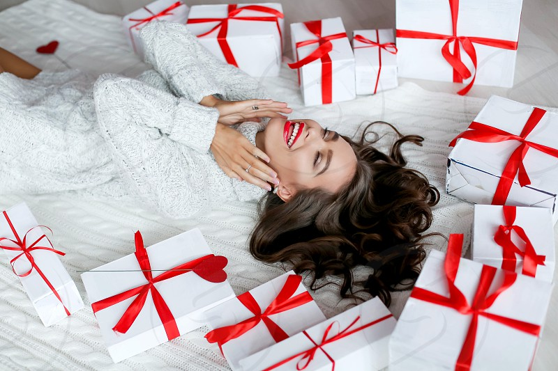 Beautiful excited smiling young woman with present gift feeling happy near christmas tree. photo