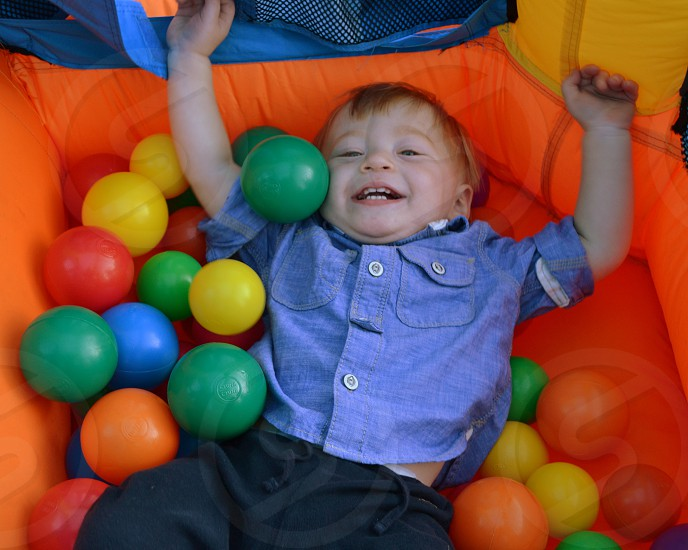 smiling toddler in ball pit photo
