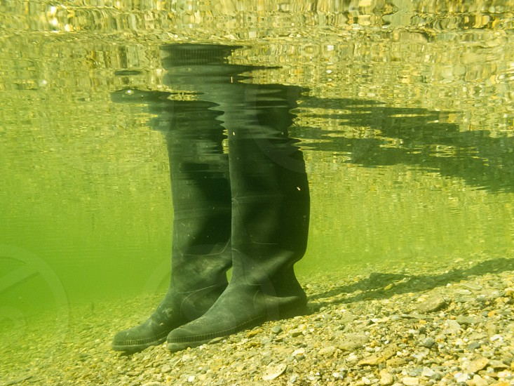 Closeup underwater view of rubber boots gumboots or waders of a person walking in shallow water of gravel and sand beach photo
