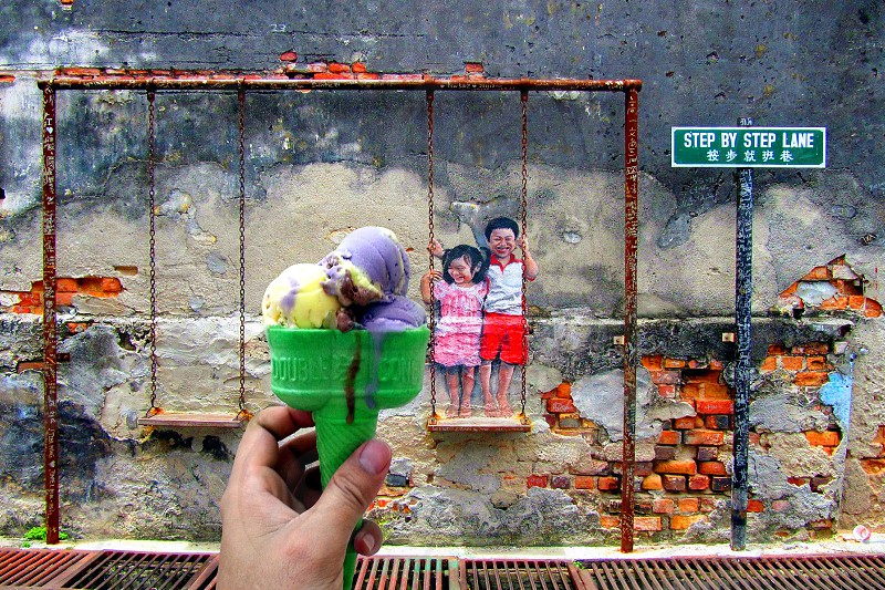 person holding green cone with ice cream toppings photo