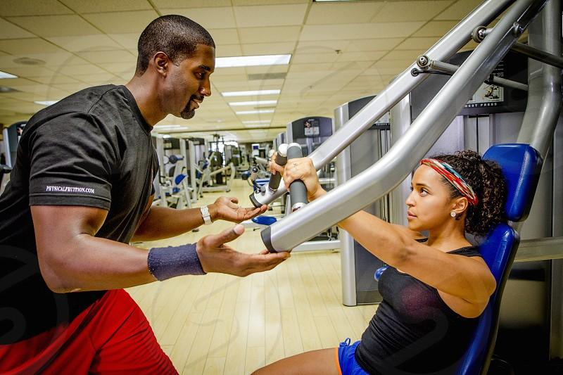 workout gym trainer. Man trains female client photo