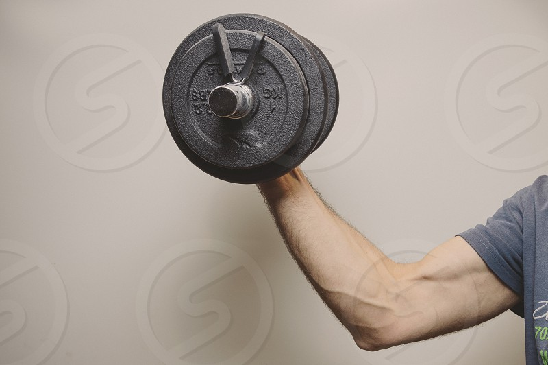 Man holding a gym weight with a muscled arm photo