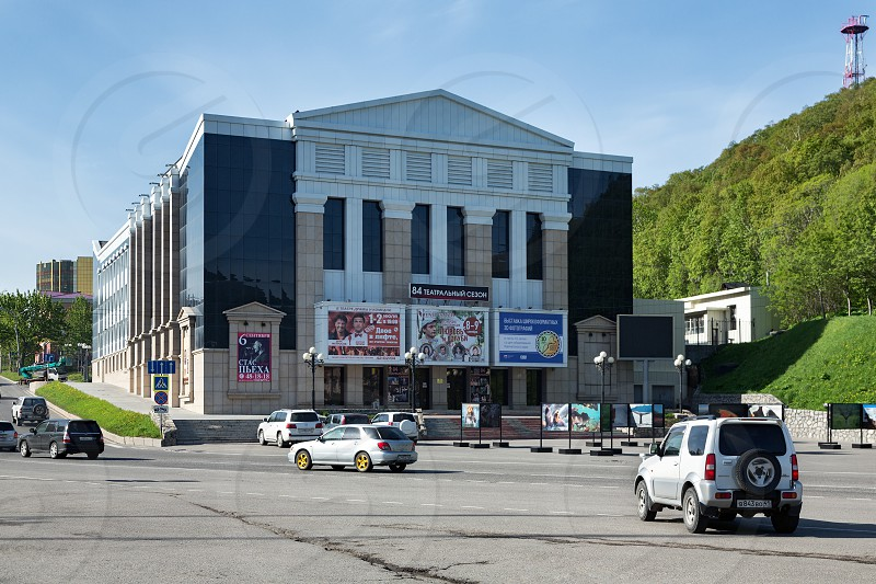 PETROPAVLOVSK-KAMCHATSKY CITY KAMCHATKA PENINSULA RUSSIA - JUNE 16 2017: Summer view on modern facade building of Kamchatka Drama and Comedy Theater in clear sunny weather. photo