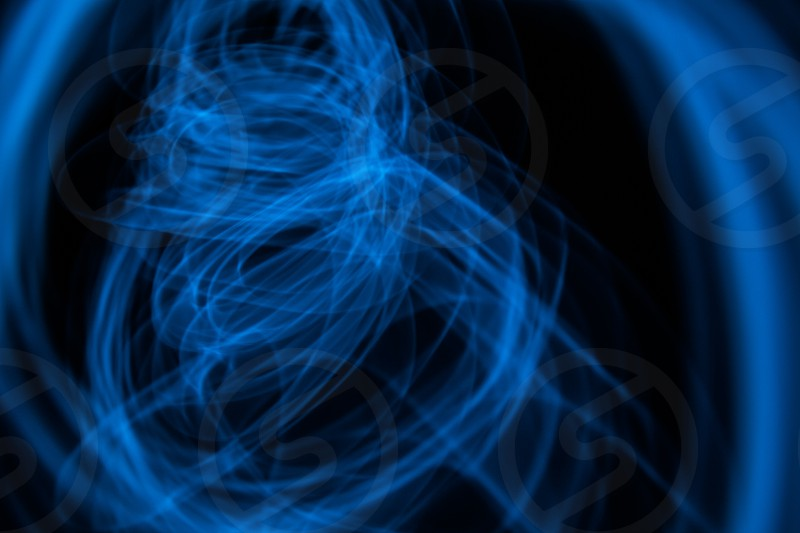 Glowing abstract curved lines.Blue colors.Black background.Done by long exposure technique. photo