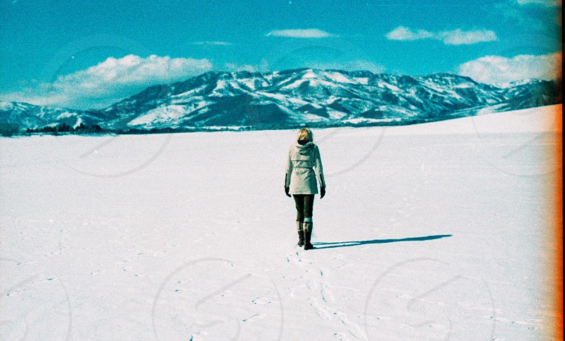 woman in gray jacket walking snow covered ground photo