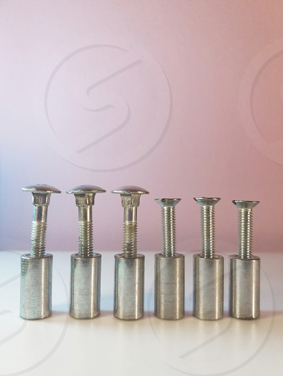 Screws with large and normal head on light background. photo