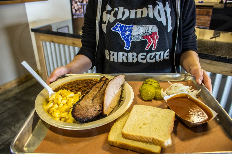 person wearing black long sleeve schmidt barbecue printed shirt serving tray full of food photo