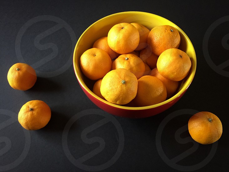 Clementines in a yellow & red bowl on black photo