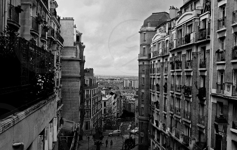 Two tourists leave Montmartre towards the open cityscape of Paris peeping through in this black and white image photo