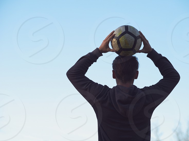 Soccer Player Posing with Football against Clear Blue Sky photo