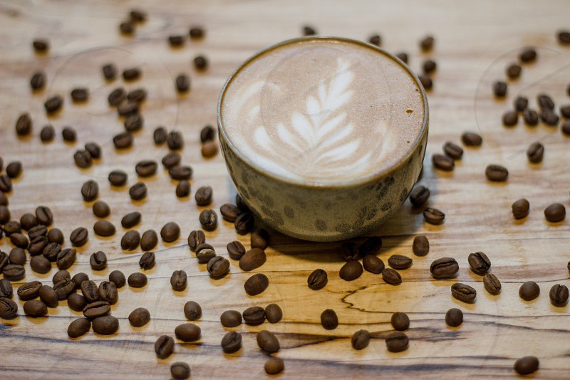 Coffee cappuccino cup with coffee beans on table photo