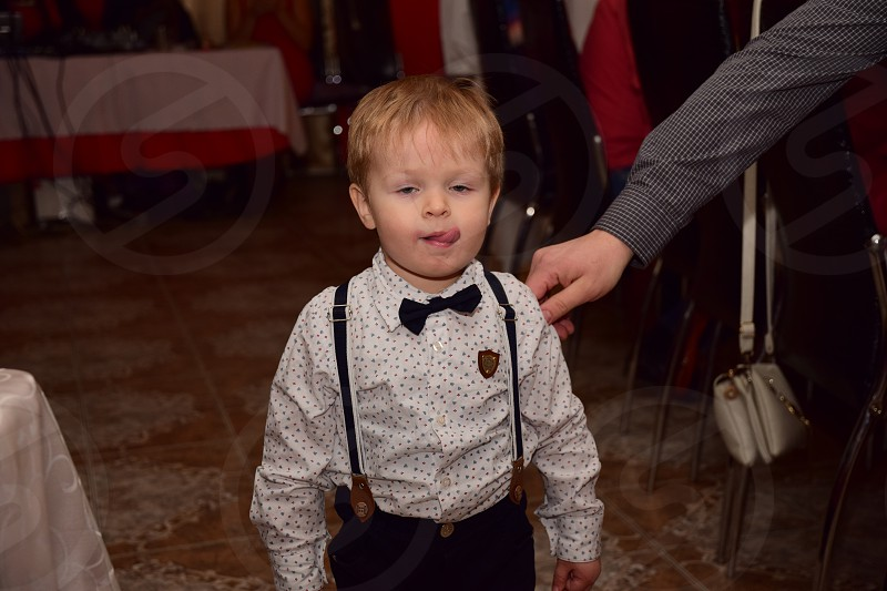boy wearing white button-up dress shirt and black pants standing licking his lips photo
