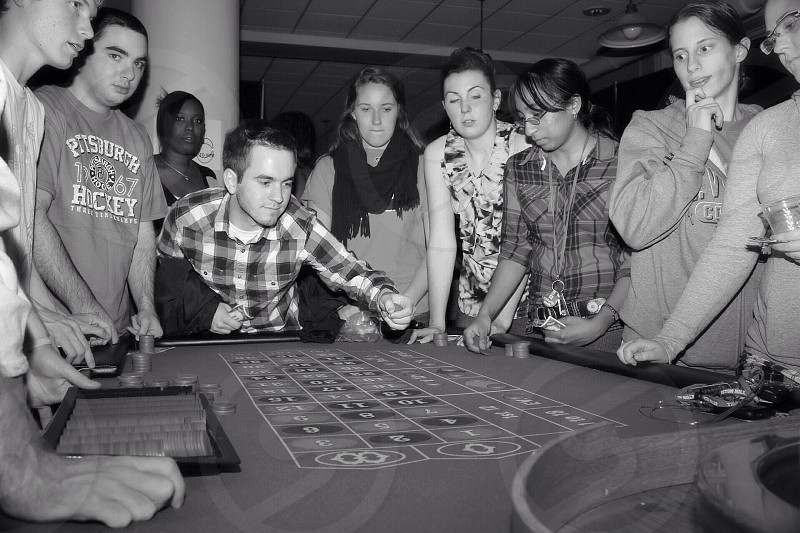 people standing around a roulette table grayscale photo photo