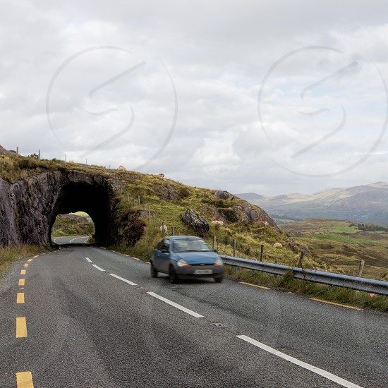 A car driving through a tunnel on the ring of Kerry Ireland road countryside sheep photo