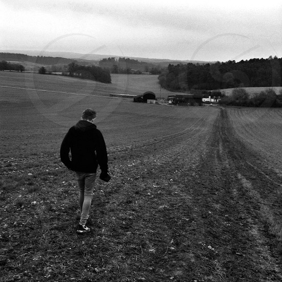 man walking on open farm field in black and white image photo