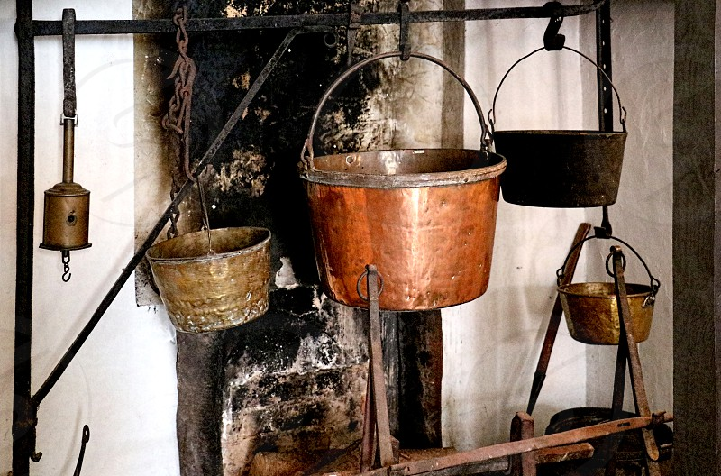 Colonial metal pots hang in a large kitchen fireplace  photo