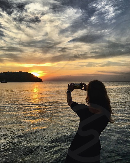 Girl taking sunset photo over water  photo