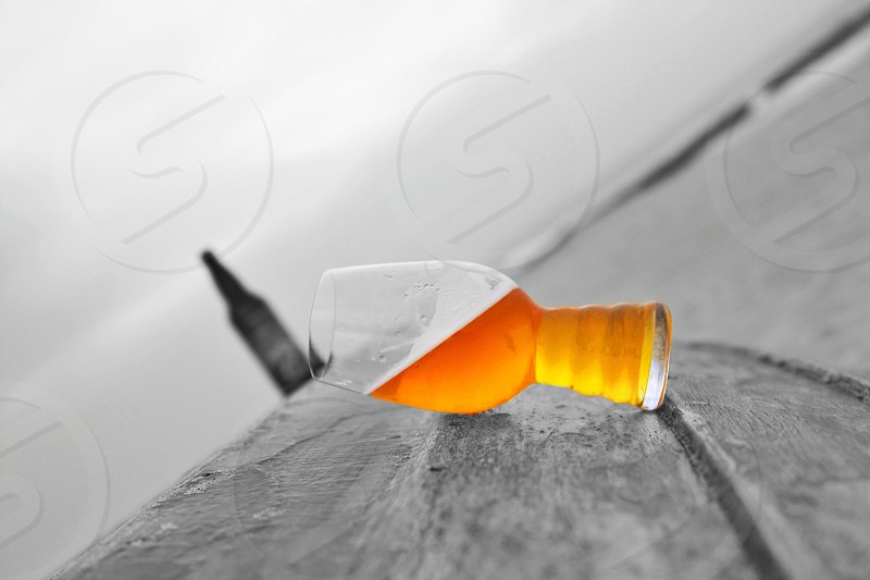 selective color photography of drinking glass in front of labeled bottle photo