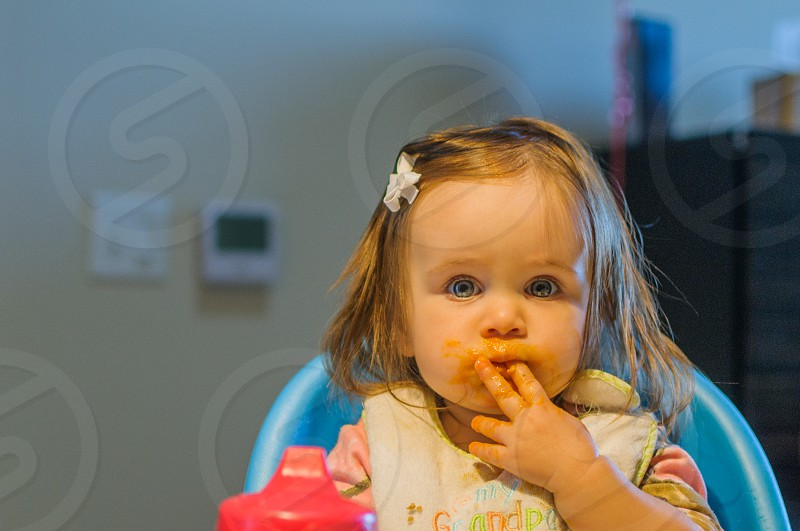 child in a high chair eating photo