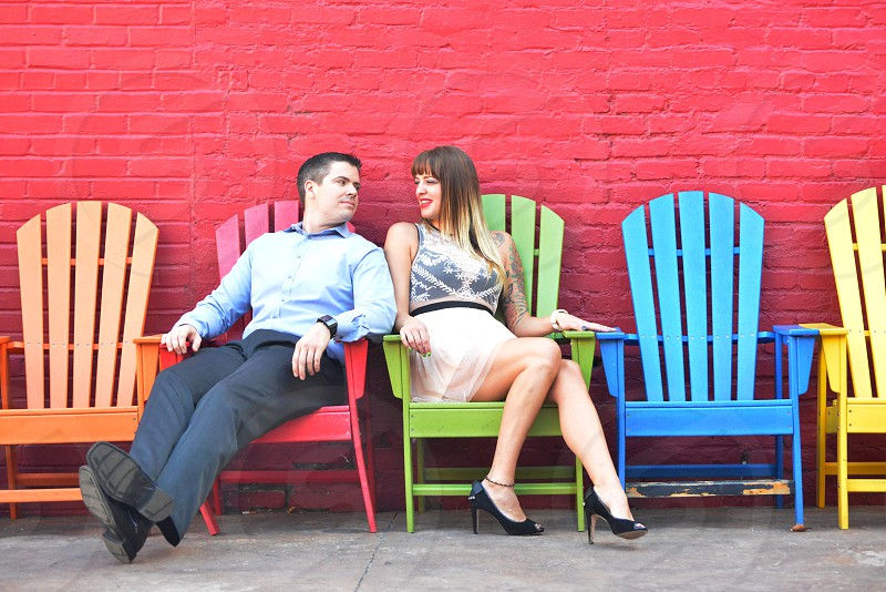 man and woman sitting in brightly painted adirondack chairs by a red painted brick wall photo