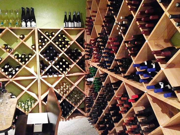 light wood standing wine bottle shelves filled with wine bottles photo