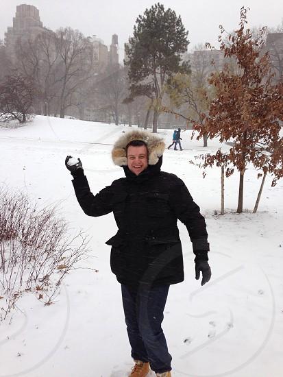 man standing on snow holding snow ball photo
