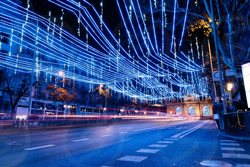 Alcala Street in Madrid at night on Christmas time. Long exposure shot with light trails of traffic and blurred people photo