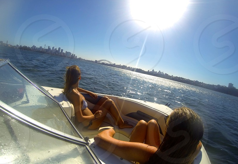 two woman with bikini in white motor boat at daytime photo