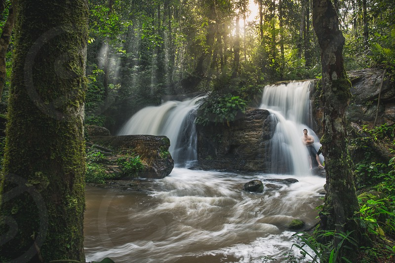 Standing in a waterfall found after hiking through the Amazon Rainforest in Brazil. photo