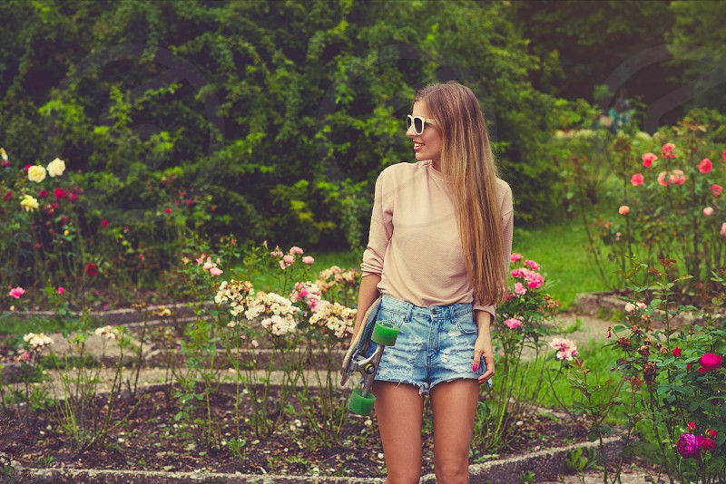 woman wearing brown crew-neck sweater and distressed blue-washed short shorts standing on flower bed photo