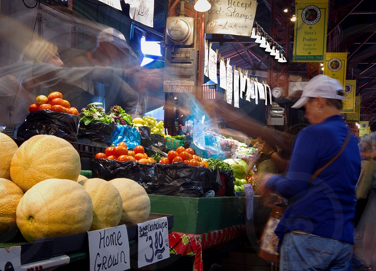 Vendors and customers are a blur of motion in a time exposure of a Saint Louis farmers market photo